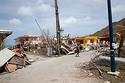 A man walks next to damaged houses destroyed by Irma during the visit of France's President Emmanuel Macron in the French Caribbean islands of St. Martin, Tuesday, Sept. 12, 2017. Macron is in the French-Dutch island of St. Martin, where 10 people were killed on the French side and four on the Dutch. Photo by Christophe Ena/Pool/ABACAPRESS.COM
