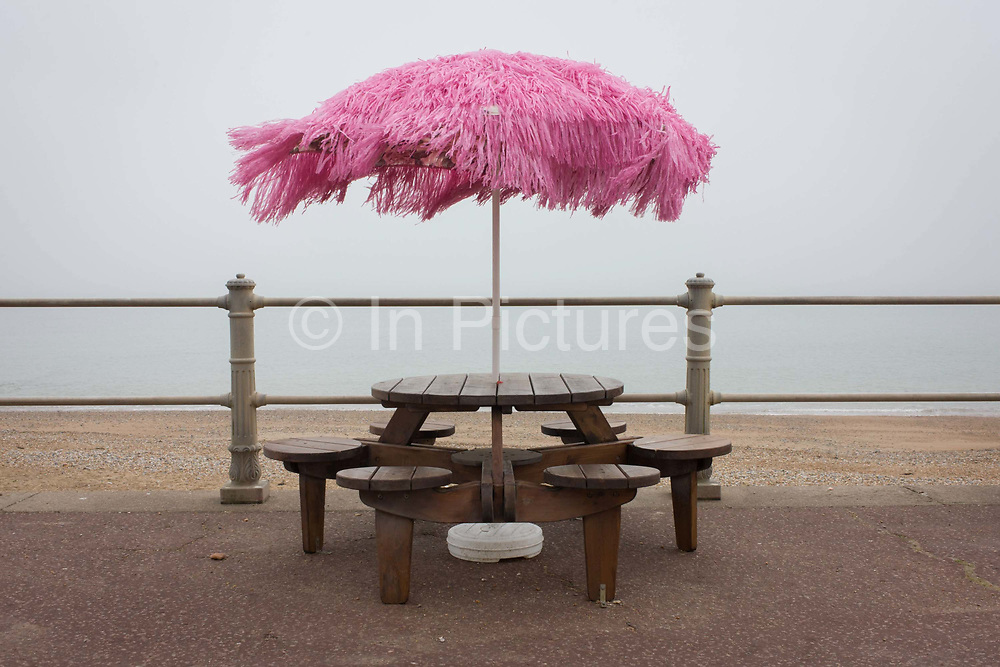 A pink-coloured parasol blows in the wind on a seafront during the winter off-season. Looking miserable and wintry, the landscape shows us the grim weather of a grey day on England's south coast - except perhaps, for the bright colours of the umbrella which blows on a sea breeze. The six-seater of a bench is empty too, as visitors to this area have yet to return to the promenades and pavements of this East Sussex coastal resort.
