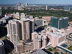 Daytime aerial view of the Texas Medical Center with the downtown Houston skyline on the horizon.