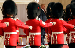 US President Donald Trump looks on as soldiers from the Coldstream Guards march past during a ceremonial welcome at Windsor Castle, Windsor.