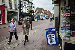 """© Licensed to London News Pictures . 17/11/2014 . Kent , UK . People walk by a local newspaper board advertising """" Election opinion poll latest """" on High Street Rochester , ahead of the Rochester and Strood by-election . Photo credit : Joel Goodman/LNP"""