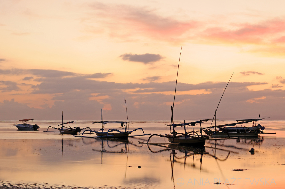 Indonesia, Bali. Outriggers on the water during a sunrise on the Sanur beach.