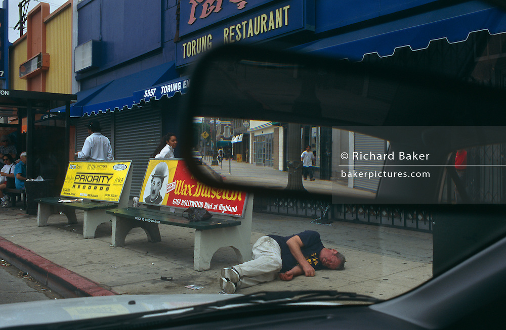 As normal life continues a man under the influence of alcohol lies unconscious in Hollywood near a poster of Charlie Chaplin.