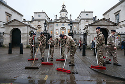 © Licensed to London News Pictures. 19/12/2019. Soldiers from the Household Cavalry sweep away puddles outside Horse Guards caused by heavy rain last night in preparation for the State Opening of Parliament. Photo credit: Alex Lentati/LNP