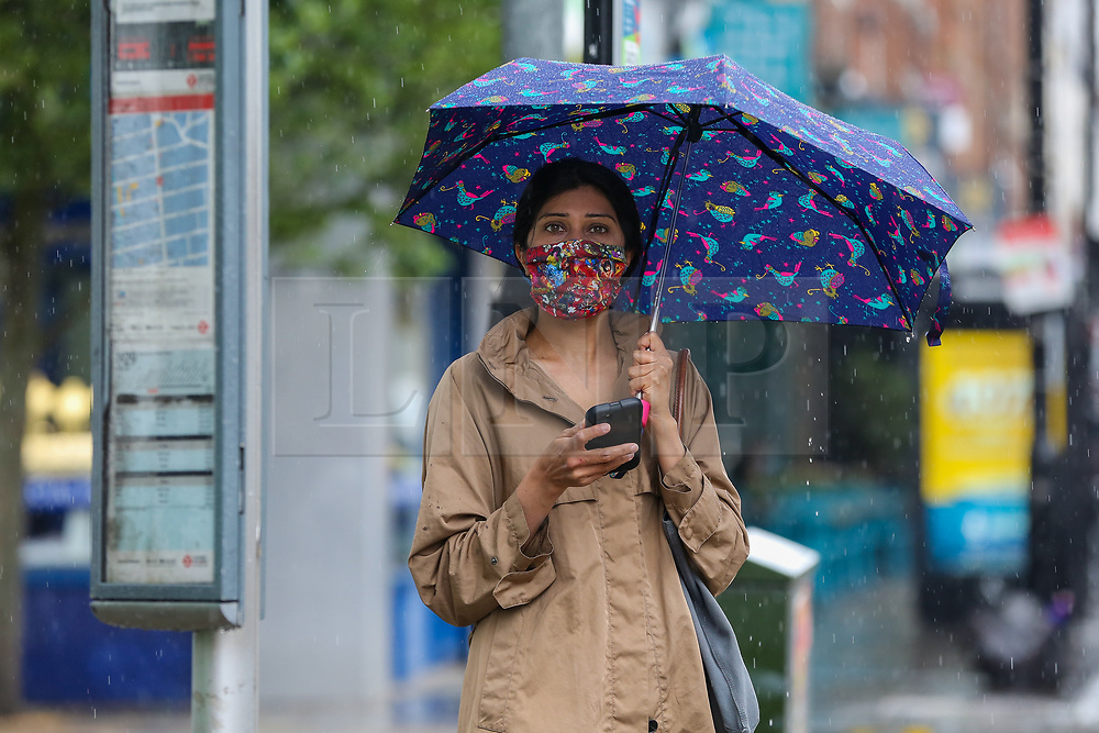© Licensed to London News Pictures. 04/06/2021. London, UK. A woman at a bus stop shelters from the rain beneath an umbrella during rainfall in north London. According to The Met Office, more rain is expected today across London and the South East of England, with the hot weather returning tomorrow. Photo credit: Dinendra Haria/LNP