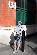 A fashionably dressed young man waits for a friend by an alley off the Covent Garden Market Piazza. London, UK