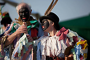 A middle aged man and woman dressed in Morris dancing attire perform for crowds visitors, english traditions. The annual Beltane celebrations at Butser ancient farm, Hampshire, marking the beginning of the British summer.