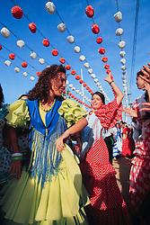Europe, Spain, Sevilla (also known as Seville) women in flamenco dresses dancing at annual Feria de Abril festival
