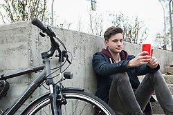 Young man text messaging on mobile phone and leaning against wall, Munich, Bavaria, Germany