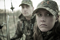 FEMALE BOWHUNTER HOLDING A BOWTECH BOW AND WEARING MOSSY OAK TREESTAND CAMO WITH A GUIDE WHOSE USING RATTLING ANTLERS