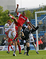 Photo: Paul Thomas.<br /> MK Dons v Swindon Town. Coca Cola League 1.<br /> 01/10/2005.<br /> <br /> Swindon's Ricky Shakes competes with MK Dons keeper and defender Dean Lewington for the ball. In the end Ricky is injured.
