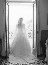 back of a bride standing in a doorway with french doors in Italy