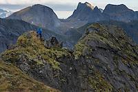 Female hiker walks along narrow ridge near Storskiva mountain peak, Moskenesøy, Lofoten Islands, Norway