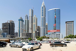 Skyline of skyscrapers and car parking lot on sand in Dubai United Arab Emirates