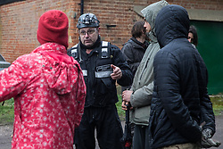 Harefield, UK. 13 January, 2020. A senior enforcement agent liaises with Stop HS2 activists observing a team of engineers constructing a gate across a public right of way leading to an activist protection camp. Part of the nearby Colne Valley protection camp was evicted by bailiffs last week. 108 ancient woodlands are set to be destroyed by the high-speed rail link and further destruction of trees for HS2 in the Harvil Road area is believed to be imminent.
