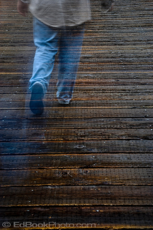 A man is walking ghostly across the Nisqually River wooden suspension bridge in Mount Rainier Natioal Park, Washington, USA