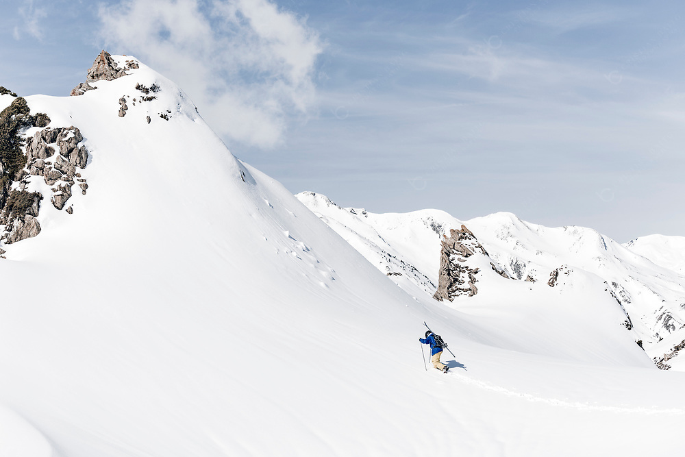 Man walking up the mountain during backcountry skiing in the Pyrenees mountains in Val d'Aran Catalonia Spain