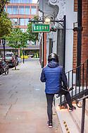 Male figure standing wearing black crash helmet outside a small hotel in Kensington, London.