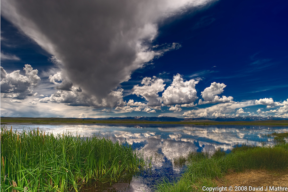 Summer Panorama Cloud and Sky Reflections at a Lake in Arapaho National Wildlife Refuge. Composite of 3 images taken with a Nikon D3 and 24 mm f/3.5 PC-E lens (ISO 200, 24 mm, f/16, 1/100 sec).