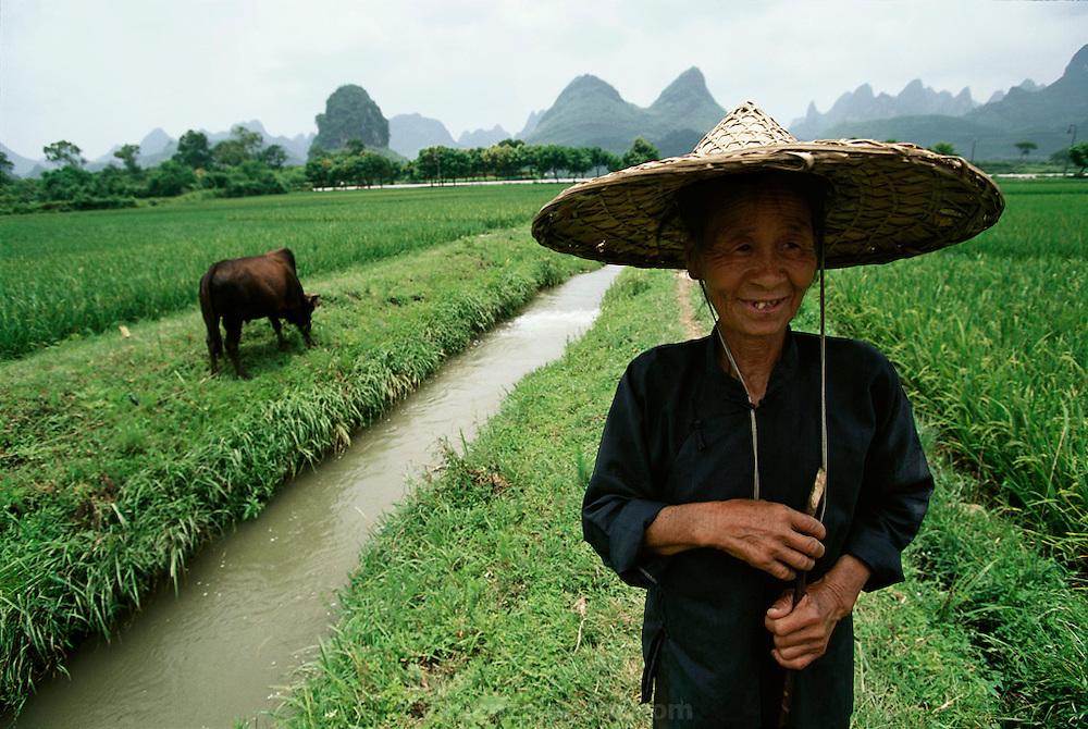 A farmer in her field with her water buffalo in Yangshuo, China.
