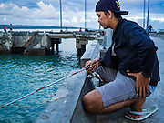18 JULY 2016 - KUTA, BALI, INDONESIA:  A man fishes on the pier at Pasar Ikan pantai Kedonganan, a fishing pier and market in Kuta, Bali.   PHOTO BY JACK KURTZ