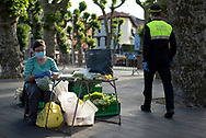 A policeman passes by as a farmer, wearing protective face mask, places the vegetables in her outdoor market stall. Irun (Basque Country). May 09, 2020. As the downscaling progresses, there are more and more businesses and commercial activities that take over their activity, after having been closed due to the blockade ordered by the Spanish government to prevent the spread of the COVID-19. (Gari Garaialde / Bostok Photo)