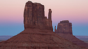 The Mittens in Monument Valley at dusk with the earth's shadow visible behind