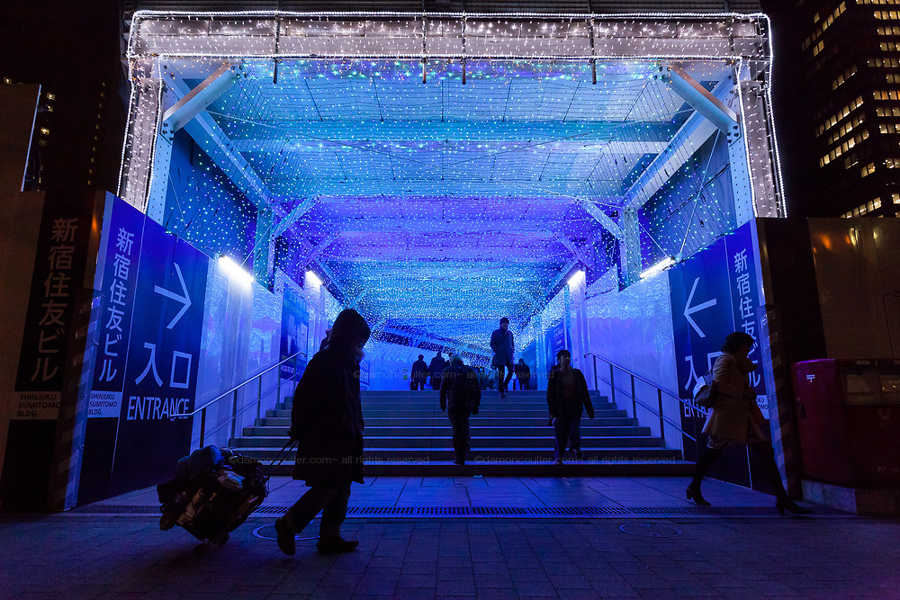A homeless man walks past a passageway decorated with colourful LED lights in Shinjuku, Tokyo, Japan. Thursday February 15th 2018