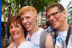 London, June 28th 2014. Proud parents show their support for their gay son as the Pride London parade proceeds through the city's streets.