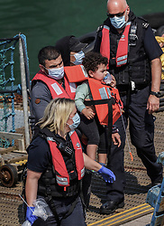 © Licensed to London News Pictures. 21/07/2021. Dover, UK. Migrants are escorted by Border Force officers as they are brought ashore at Dover Harbour in Kent after crossing the English Channel. It is being reported that at least 430 migrants crossed the English Channel to the UK on Monday, a new single day record. Photo credit: Stuart Brock/LNP