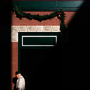 The midday sun casts distinct shapes over buildings in downtown as a man walks down Quarrier Street in Charleston, W.V., on Monday, December 17, 2018.