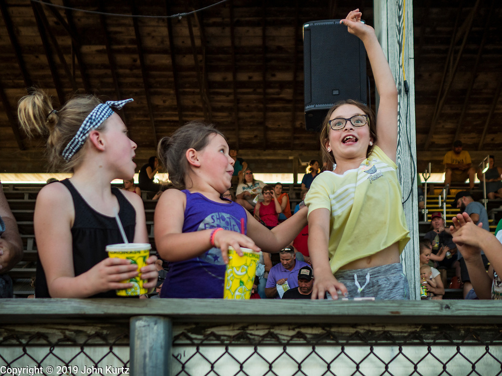 """26 JUNE 2019 - CENTRAL CITY, IOWA: Girls cheer during the """"Mutton Bustin' """" contest at the Linn County Fair. Mutton Bustin' is an event for young children. They ride sheep bareback for six seconds. Summer is county fair season in Iowa. Most of Iowa's 99 counties host their county fairs before the Iowa State Fair, August 8-18 this year. The Linn County Fair runs June 26 - 30. The first county fair in Linn County was in 1855. The fair provides opportunities for 4-H members, FFA members and the youth of Linn County to showcase their accomplishments and talents and provide activities, entertainment and learning opportunities to the diverse citizens of Linn County and guests.      PHOTO BY JACK KURTZ"""