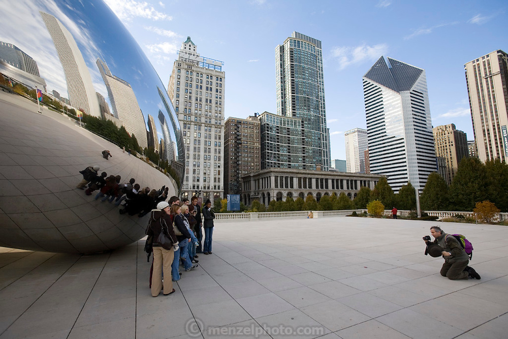 A group of friends have their picture taken in front of The Cloud Gate, a large mirroring metal sculpture at Millennium Park, Chicago, Il, USA. It visually bends the cityscape and people that pass by, and under. By British artist Anish Kapoor.