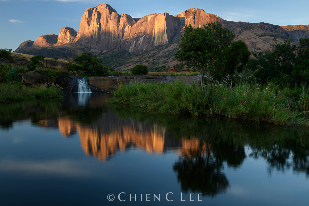 Morning sunlight reaches the top of the Tsaranoro Massiff, an enormous 800m high granite cliff in southeastern Madagascar.