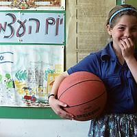 Israel, Jerusalem, Moshav Qeshet, Portrait of young schoolgirl holding basketball at school in Golan Heights