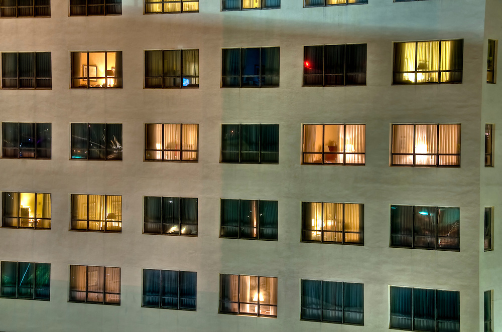 View of Hotel windows at night with reflections and inside view.