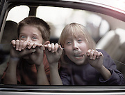 Two siblings make goofy faces and hold onto the half cracked window of the family car