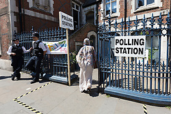 © Licensed to London News Pictures. 11/06/2015. London, UK. A woman enters a polling station in Brick Lane, Tower Hamlets, east London. Tower Hamlets residents go to the polls today to vote for a new Mayor of Tower Hamlets after Lutfur Rahman was removed from office for fraud and corrupt practices by an election court earlier this year. Photo credit : Vickie Flores/LNP