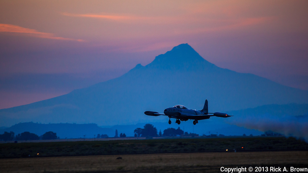 """Greg Colyer flying a """"dirty"""" pass in his Canadair CT33 past Mt. Hood at sunset at the Airshow of the Cascades."""