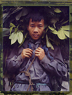 Polaroid 79 portrait of a man carrying a bundle of leaves in Ha Giang Province, Northern Vietnam, Southeast Asia