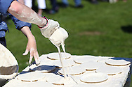Coxheath, Kent - Saturday, May 22nd 2010: Fresh custard pies are made ready at the World Custard Pie Championships at Coxheath near Maidstone, Kent. The first championship was held in 1967 in Coxheath using a special custard recipe developed by Richard Hearn aka Mr Pastry. The championship is made up of teams competing in heats, semi finals and the final, with the number of pies available per team increasing from 5 in the heats to 10 in the final. 6 points are scored for a direct hit on the face, 3 points for the shoulders or upwards, 1 point for any other part of the body, and points are deducted for misses. A discretionary 5 points can be awarded for the most amusing and original throwing technique. The event is part of the Rotary Club funday. (Pic by Andrew Tobin/SLIK Images)