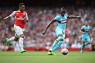 Diafra Sakho of West Ham United makes a break with Francis Coquelin of Arsenal chasing. Barclays Premier League, Arsenal v West Ham Utd at the Emirates Stadium in London on Sunday 9th August 2015.<br /> pic by John Patrick Fletcher, Andrew Orchard sports photography.