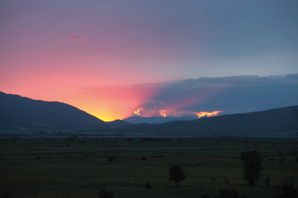 The northern part of Livansko Polje field -  karst plateau (arguably the largest karst field in the world) and the Dinara mountain range (on the left) at sunset. Zdralovac area in the foreground. This is an area that was affected by Balkan war (1991-1995) and now is plenty of mine fields. May 2009. <br /> Bosnia-Herzegovina.