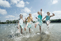 Group of friends splashing water in the lake, Bavaria, Germany