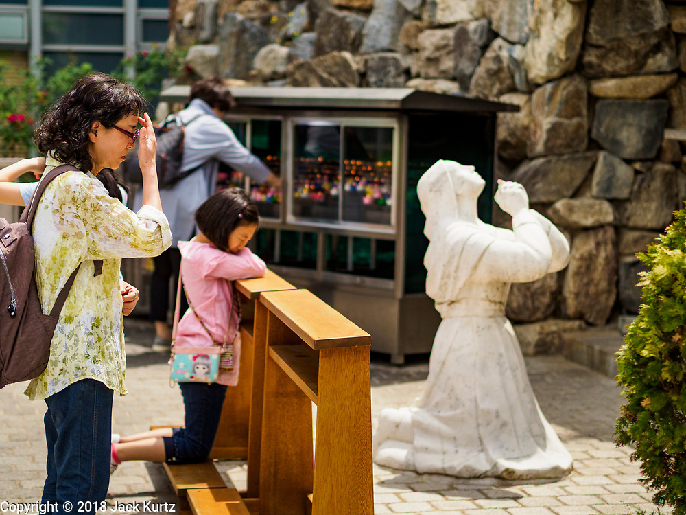 10 JUNE 2018 - SEOUL, SOUTH KOREA: Women pray in a grotto at the Catholic cathedral in Seoul.    PHOTO BY JACK KURTZ