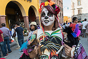 A woman dressed in costume for Day of the Dead festival shows off her costumed dogs at the Jardin Principal in San Miguel de Allende, Guanajuato, Mexico. The week-long celebration is a time when Mexicans welcome the dead back to earth for a visit and celebrate life.