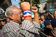 """15 JANUARY 2014 - BANGKOK, THAILAND:  SUTHEP THAUGSUBAN, former Deputy Prime Minister of Thailand and leader of the Shutdown Bangkok anti-government protests, walks up Sukhumvit Road in Bangkok leading a protest march. Tens of thousands of Thai anti-government protestors continued to block the streets of Bangkok Wednesday to shut down the Thai capitol. The protest, """"Shutdown Bangkok,"""" is expected to last at least a week. Shutdown Bangkok is organized by People's Democratic Reform Committee (PRDC). It's a continuation of protests that started in early November. There have been shootings almost every night at different protests sites around Bangkok. The malls in Bangkok are still open but many other businesses are closed and mass transit is swamped with both protestors and people who had to use mass transit because the roads were blocked.   PHOTO BY JACK KURTZ"""