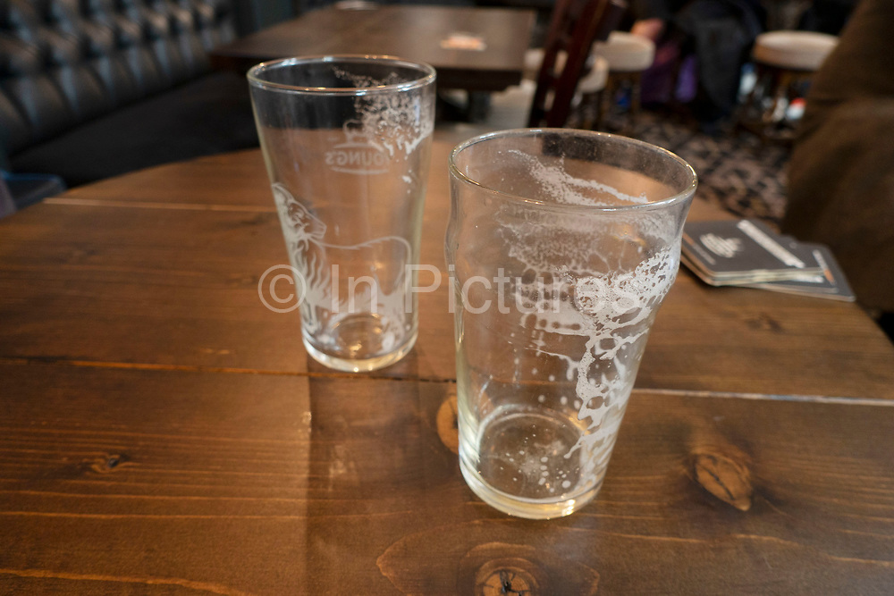 Two empty pint glasses of beer in a pub in London, United Kingdom.