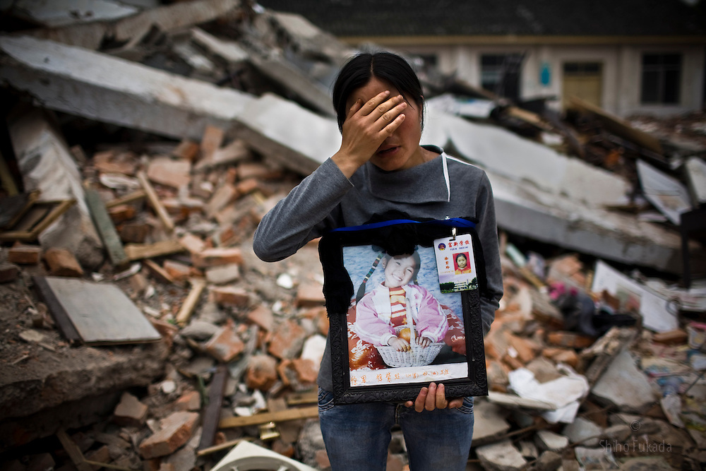 """Xiang Xiao Fang, 31, holding a picture of her daughter Xu Li Ling, 10, at Fuxin No.2 Primary  School in Mianzhu, Sichuan province May 24, 2008. """"I want to hug her again, but all I have left now is her picture. I spent all my tears."""""""