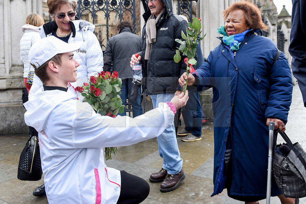 """© Licensed to London News Pictures. 08/03/2017. London, UK. A woman receives roses.  A flashmob takes place in Parliament Square as part of International Women's Day.  Apparently backed by the Russian government, a giant balloon is unsuccessfully inflated bearing the text """"From Russia With Love"""" and """"#makehersmile"""" with organisers handing out roses to unsuspecting female passers by. Photo credit : Stephen Chung/LNP"""